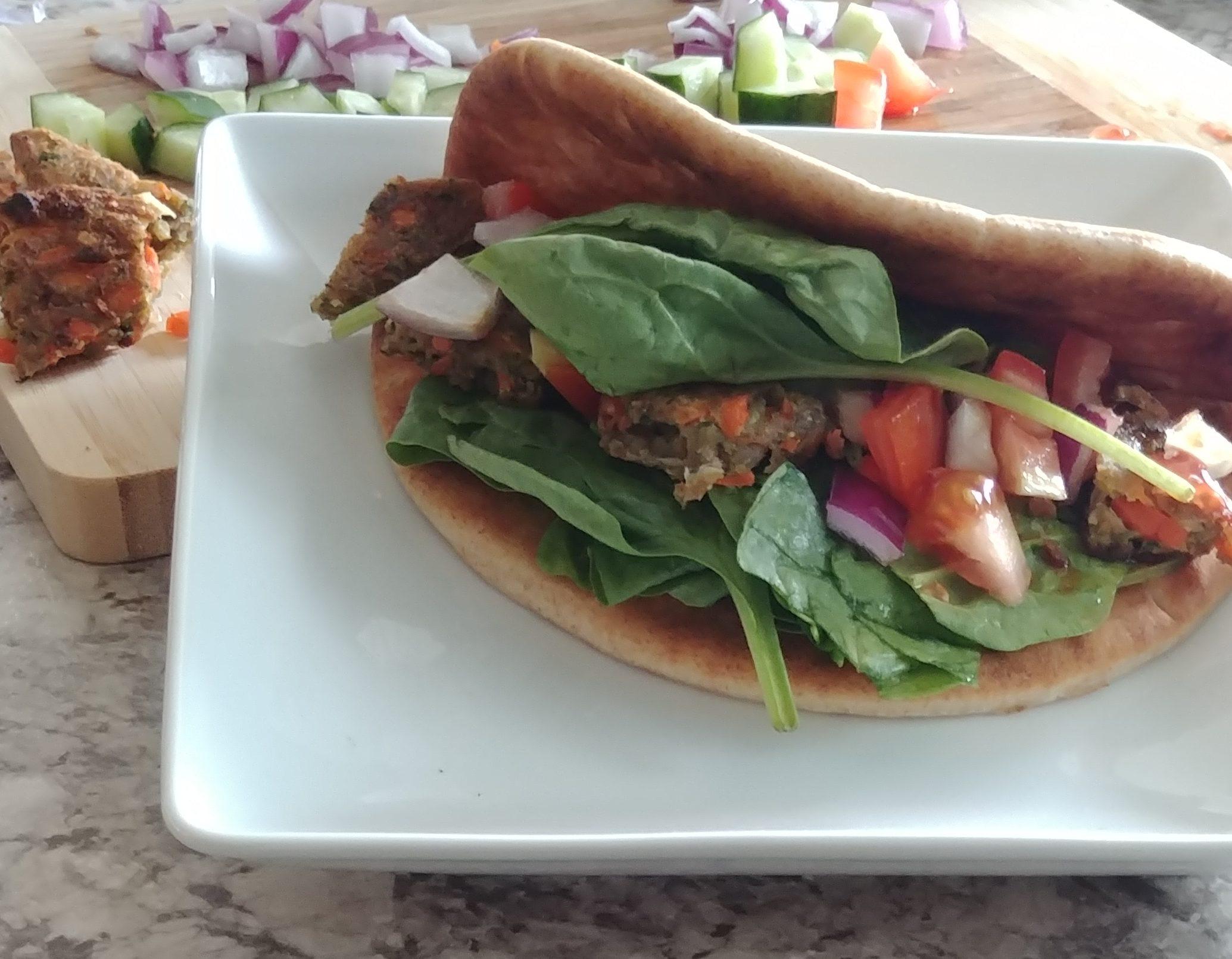 Veggie Burger Pita Wrap with cut veggies in background