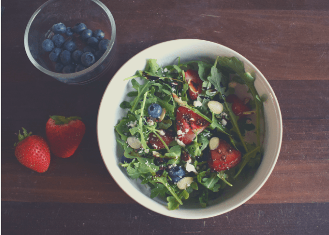 Balsamic Berry Arugula Salad in a bowl topped with feta cheese, sliced almonds, and balsamic glaze