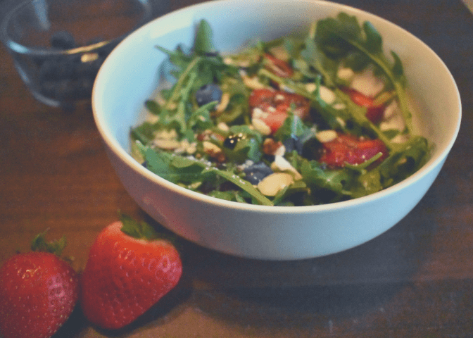 Strawberry and Blueberry Arugula Salad topped with feta cheese, sliced almonds, and balsamic glaze