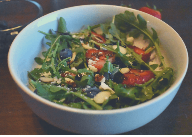 Bowl of berry arugula salad topped with feta, sliced almonds, and balsamic glaze