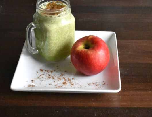 Glass of apple pie protein shake next to an apple
