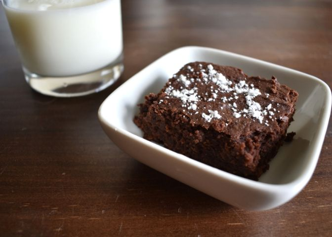 A peanut butter black bean brownie sprinkled with powdered sugar next to a glass of milk