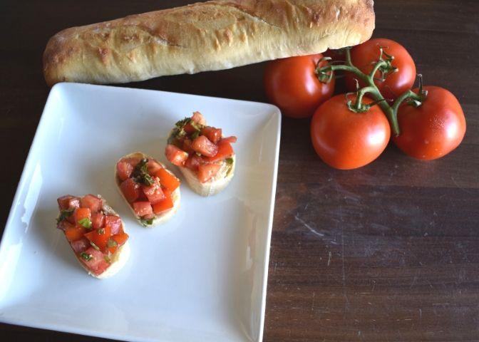 plate of tomato basil bruschetta on sliced baguettes